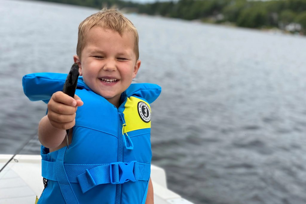 young boy excited about fish he has in his hand, wearing blue childs PFD